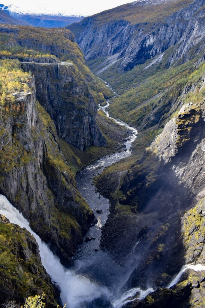 A rocky green valley with Vøringfossen waterfall running through it in Norway. Vøringfossen is a must do in your 5 days in Bergen.