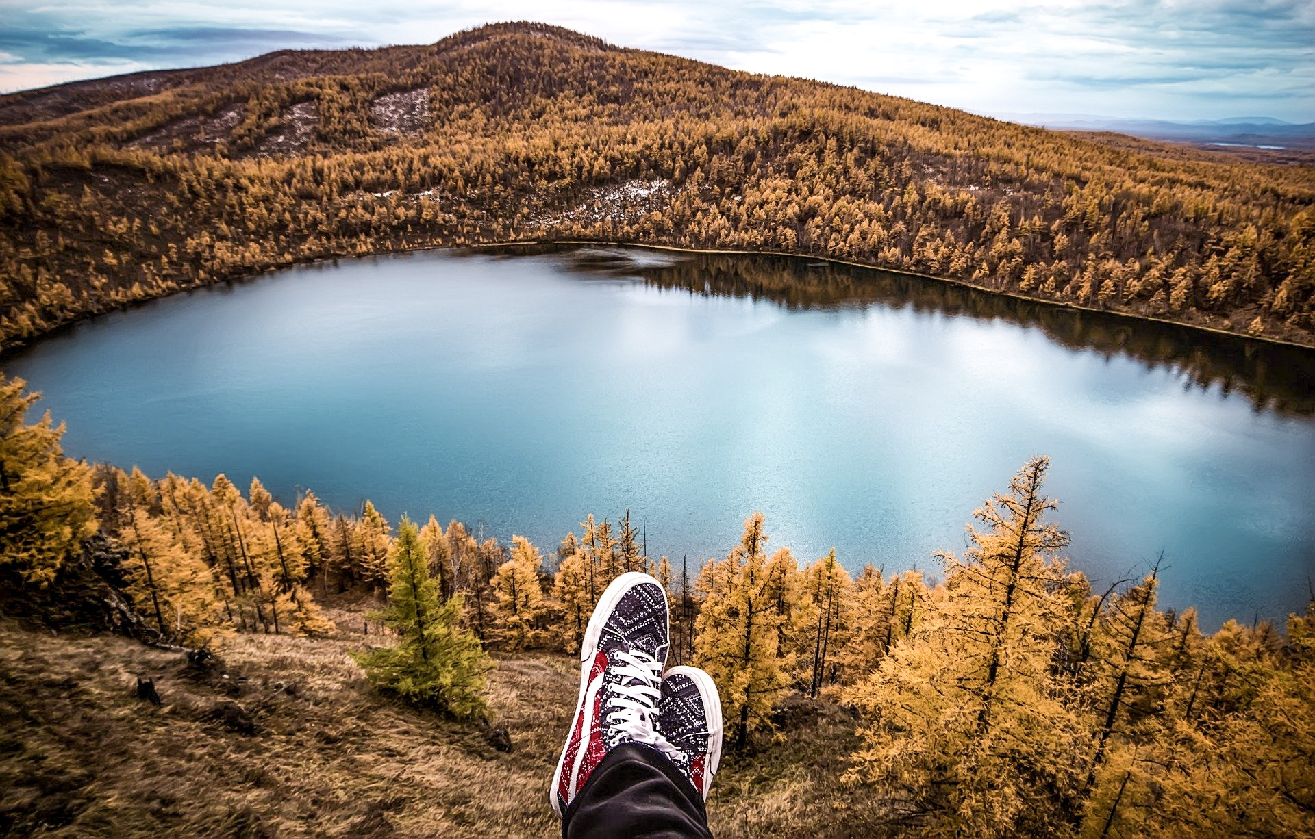 A mountain and lake view with some feet wearing trainers. Why I decided to start a blog and travel solo