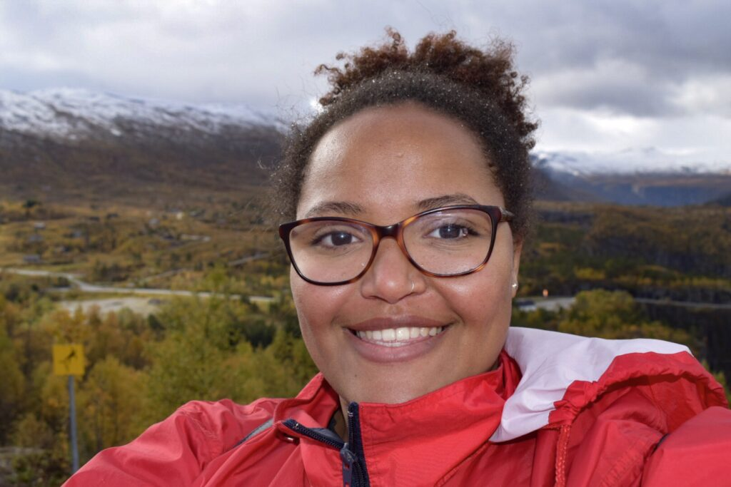 Imani stands smiling in front of snow capped mountains in Vøringfossen  wearing a red rain jacket and glasses on a fjord tour from Bergen.