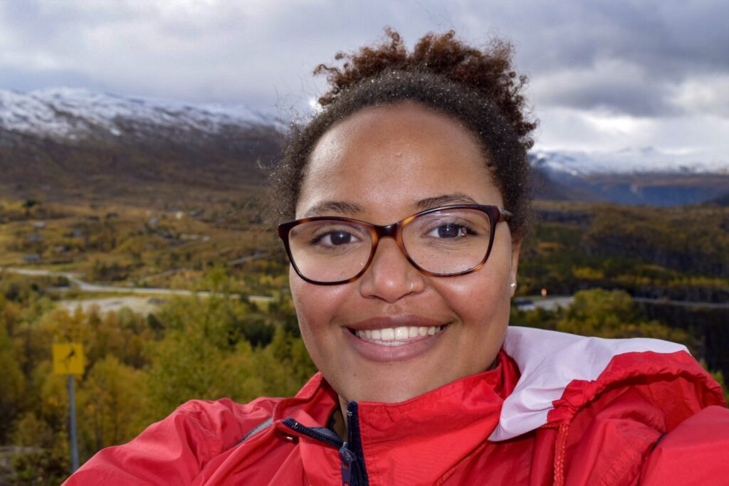 Imani stands atop a cliff in Bergen in the snow smiling and wearing a read jacket.