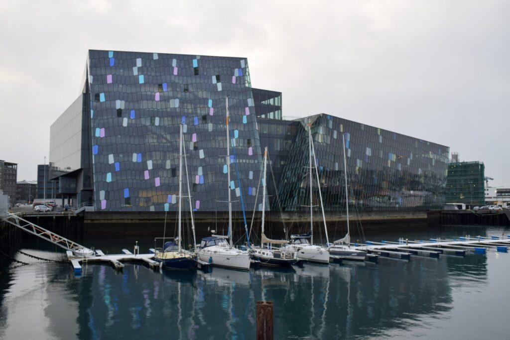 Harpa concert hall in Reykjavik by the water with several boats in front during winter in Iceland.