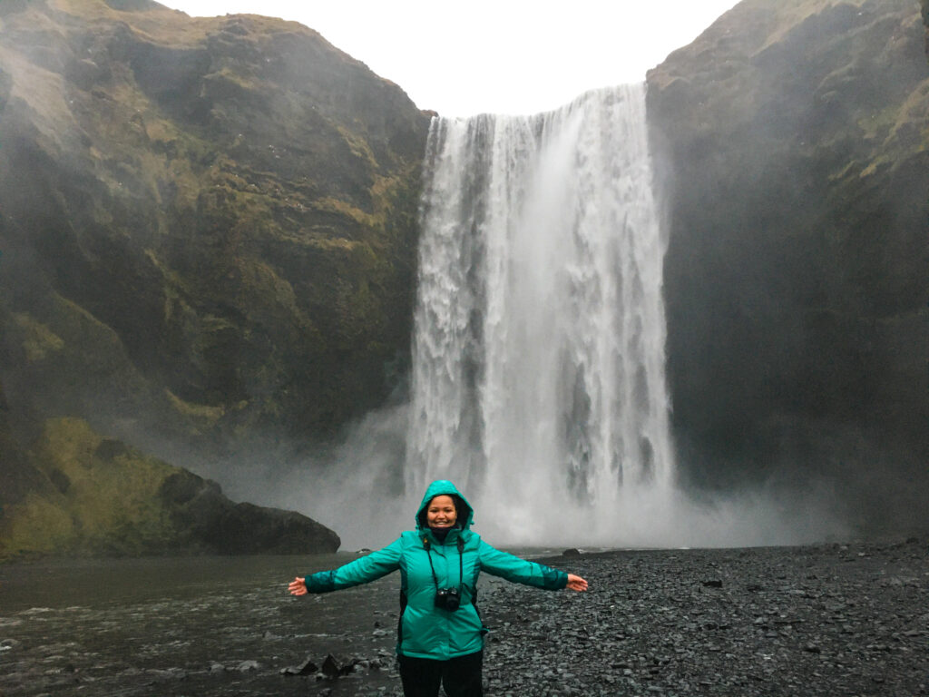 A woman in a green jacket with a camera stands arms outstretched in front of Skógafoss waterfall in Iceland in winter.