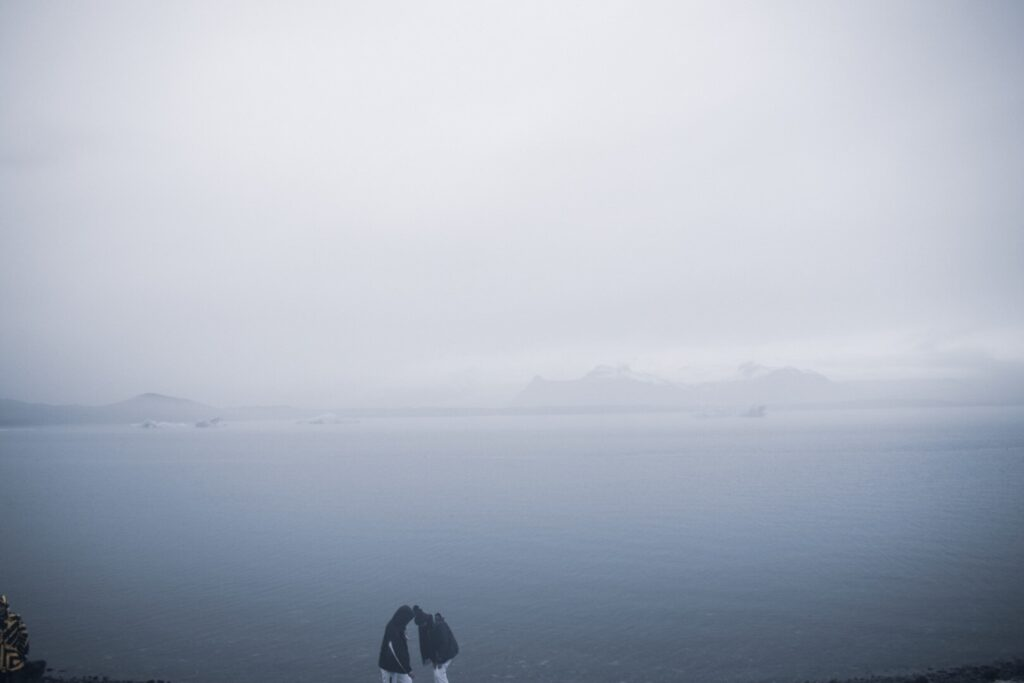A misty image of two people huddled together infront of Jökulsárlón Glacier Lagoon in Iceland, one of the best things to see and do in Iceland in winter.