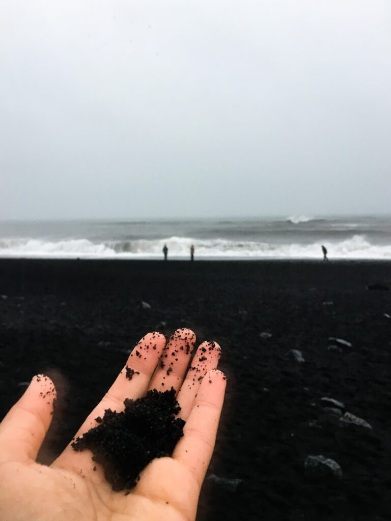 Hand holding black sand at Reynisfjara black sand beach in Iceland. Visiting a black sand beach is one of the best things to do in Iceland In winter.