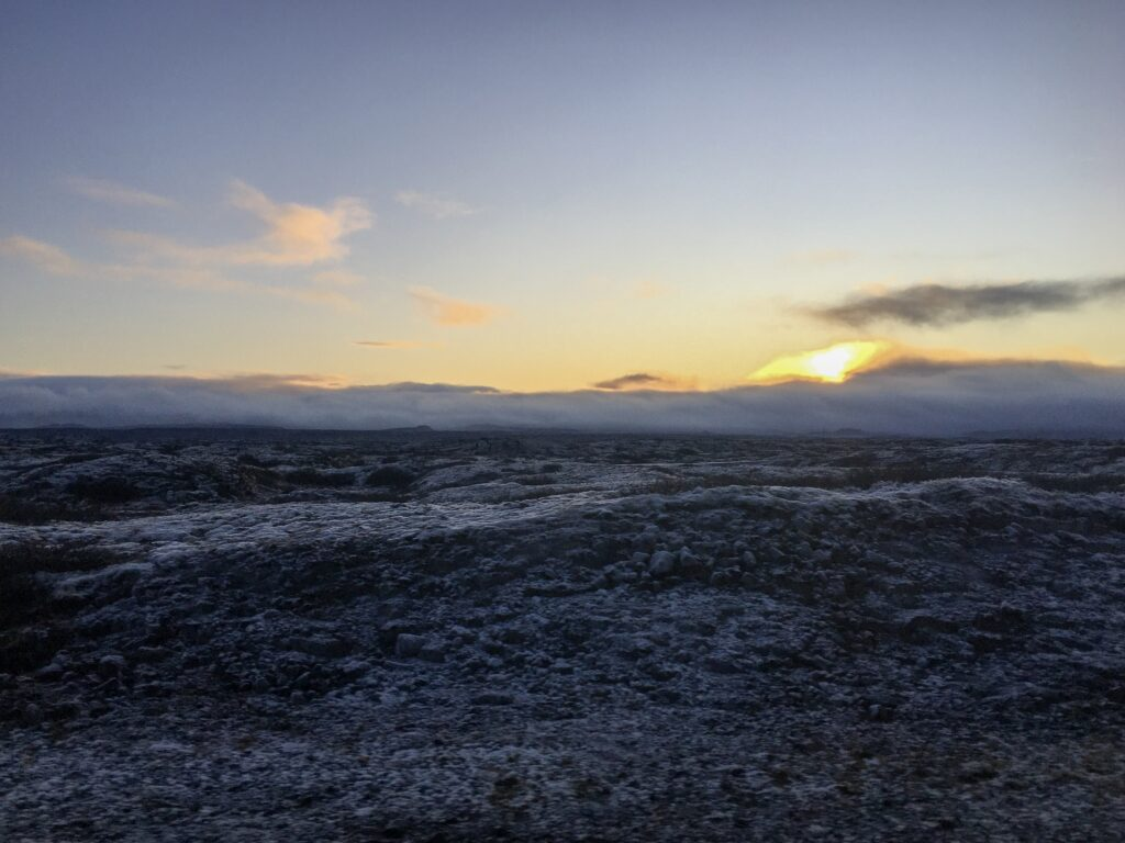 A bright yellow sunrise with blue sky and clouds above a lava field in Iceland in winter.