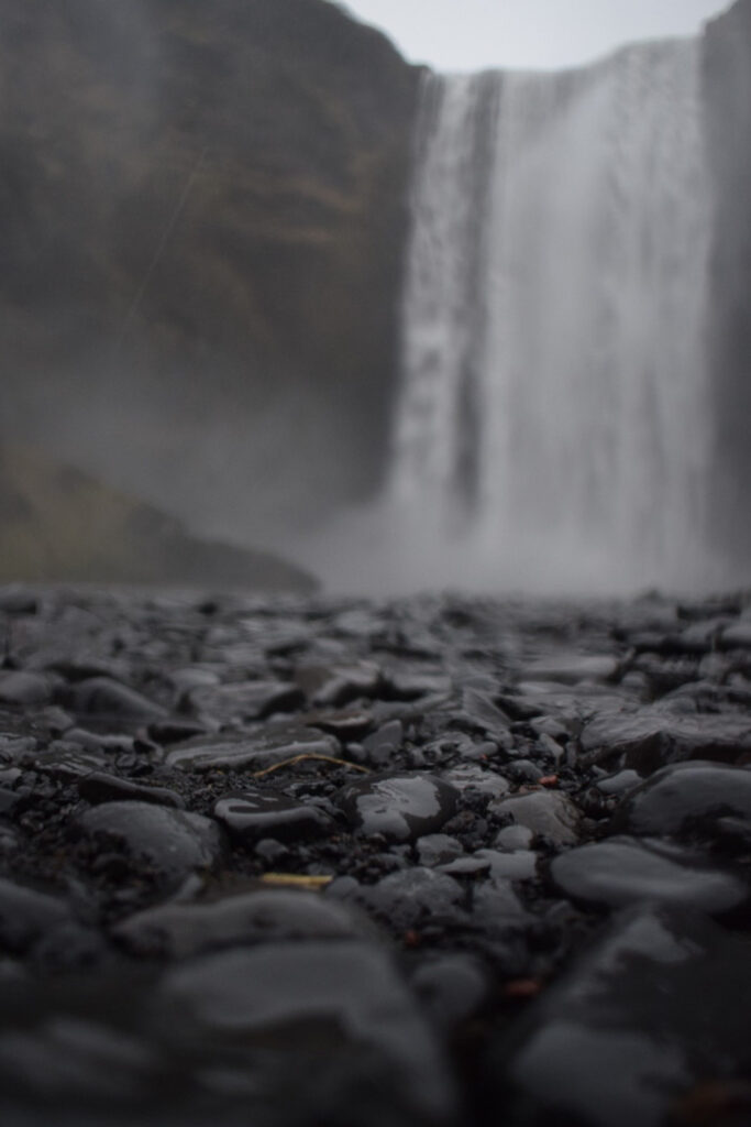 Black sand and pebbles in Iceland in winter with Skógafoss waterfall in the background.