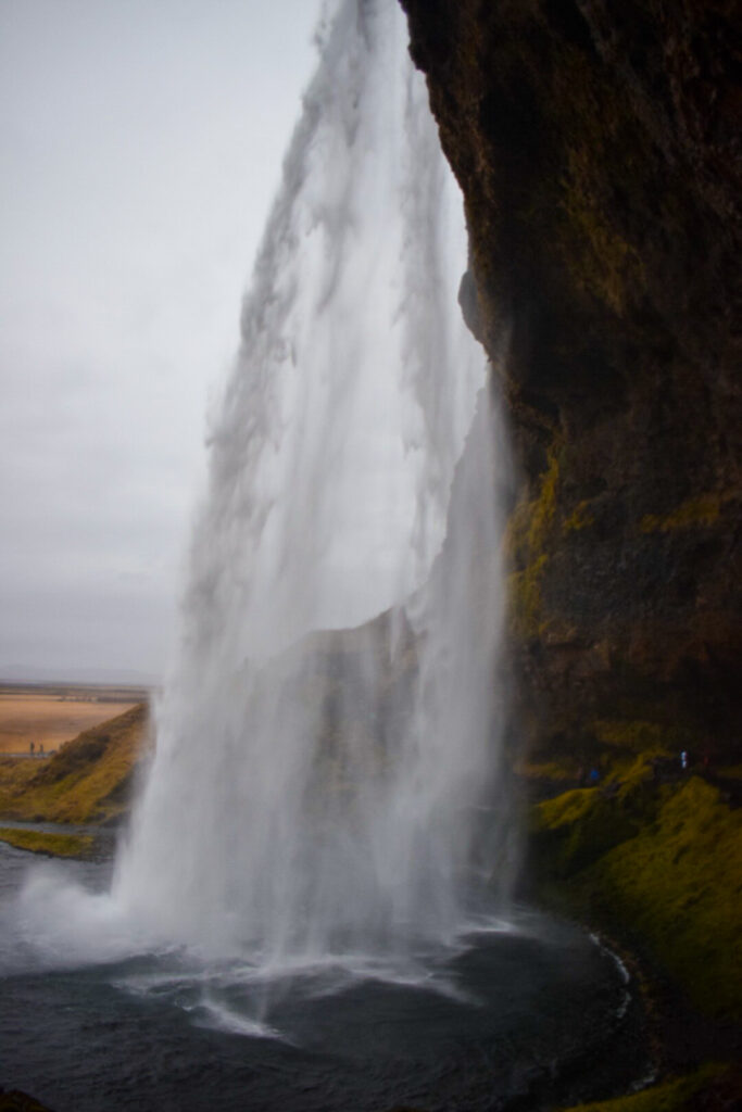 Walking behind a Seljalandsfoss waterfall in Iceland, a great thing to do do in Iceland in winter if it's not too icy.