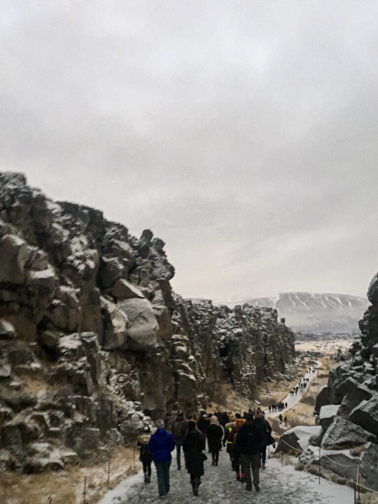 Tourists walk through a rocky canyon in thingvellir national park in Iceland in winter.