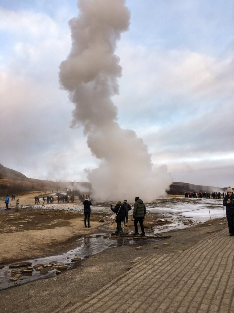 People stand around strokkur geysir in Iceland at winter after it has erupted.