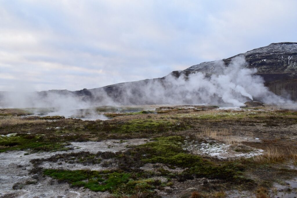Steam rises from a geothermal hot spring area in Iceland during winter.