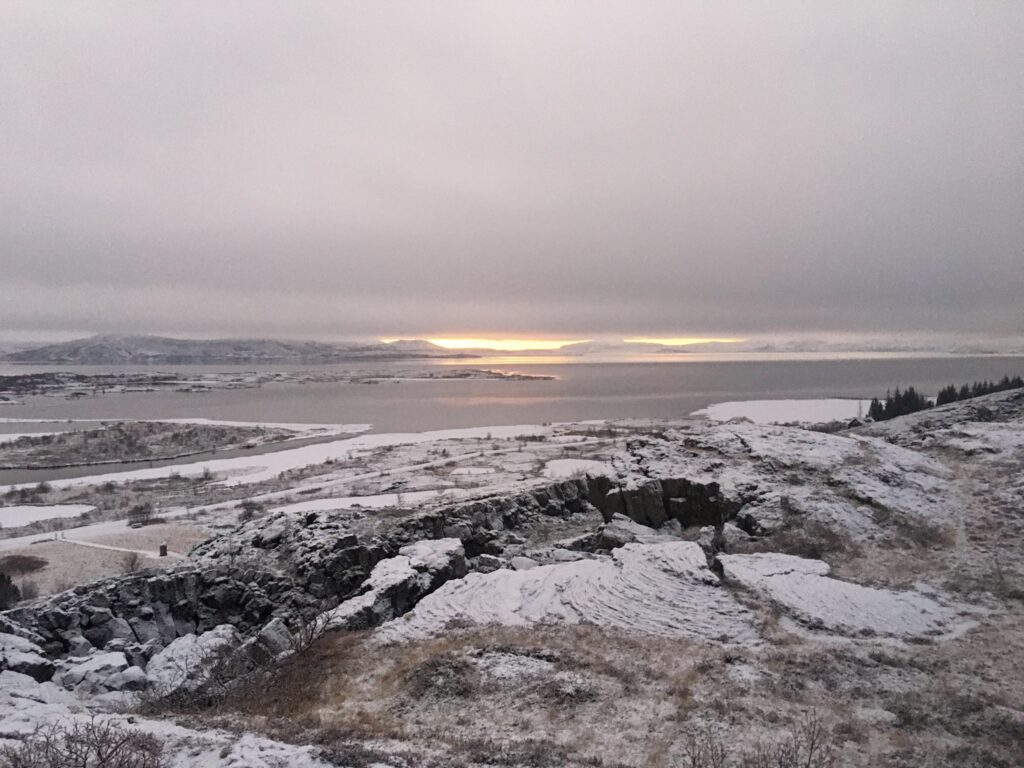A rocky snowy winter landscape with water and a sunrise in thingvellir National Park in Iceland.