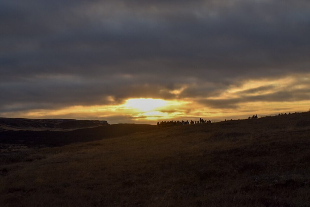 A vibrant yellow sunrise in Iceland in winter with a dark cloudy sky over brown grassy hills with a queue of people in the background.