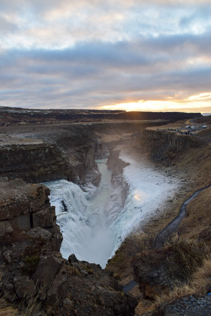 Gulfoss waterfall in Iceland semi frozen over with a sunset in the background. Gullfoss is one of the best things to do in Iceland in winter.