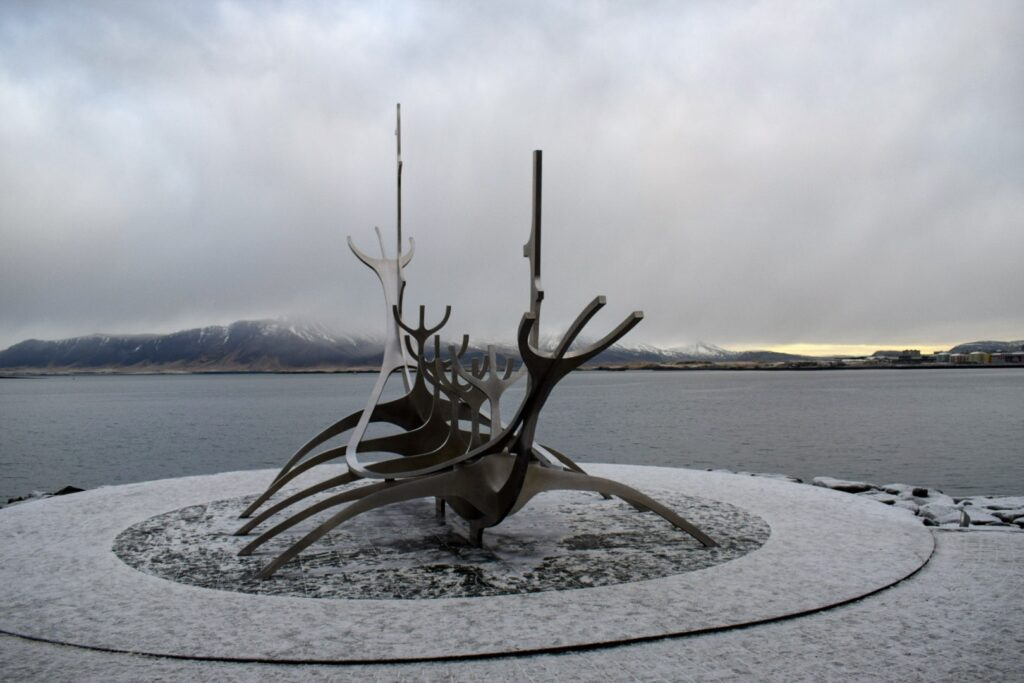 Sun voyager- a metal sculpture of a Viking boat at Reykjavik harbour with the sea and mountains in the background in Iceland in winter.