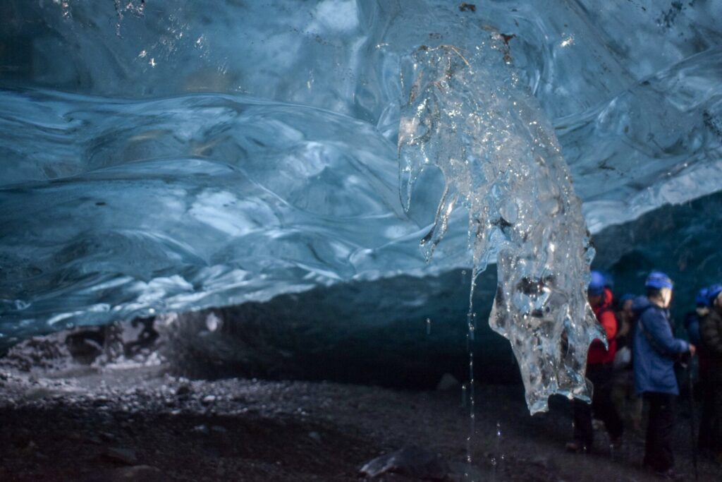 An iceberg on the wall of a blue ice cave in Iceland in winter drips with water.