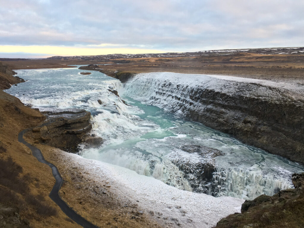 Gulfoss waterfall in Iceland partly frozen. Visiting Gullfoss is one of the best things to do in Iceland in winter.