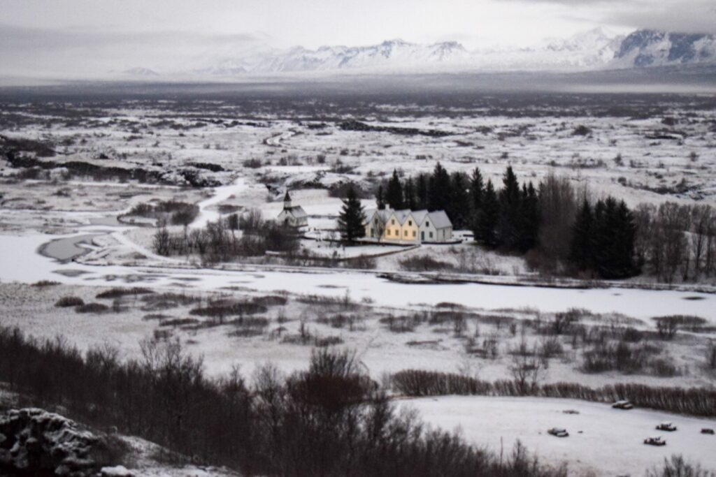 Four houses and a church in a remote, snowy scene in thingvellir park in Iceland in winter.
