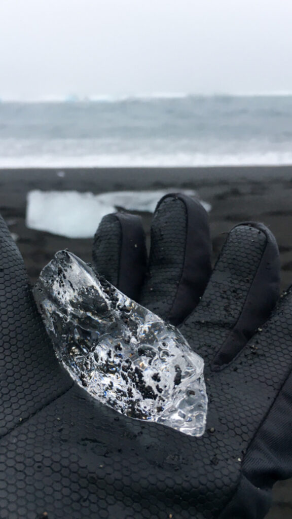 A gloved hand holding a piece of glacier at diamond beach. Seeing the glacier pieces sparkling on diamond beach is one of the best things you can do in Iceland in winter.