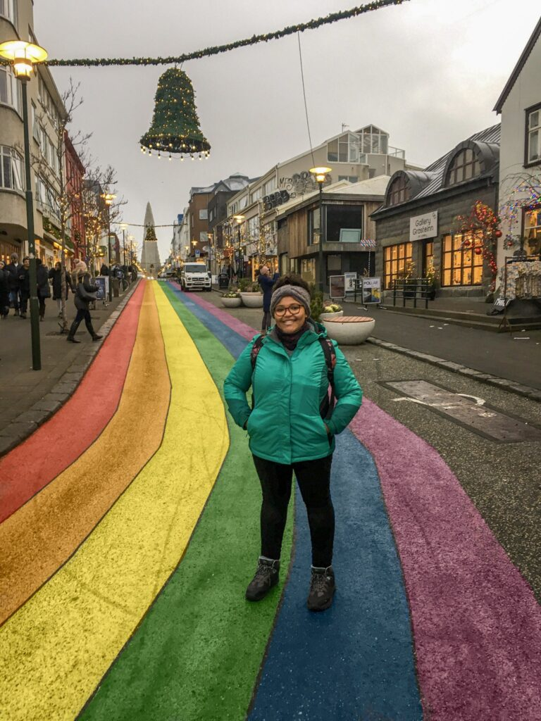 Imani posing on a rainbow coloured street in Reykjavik, Iceland, in winter.