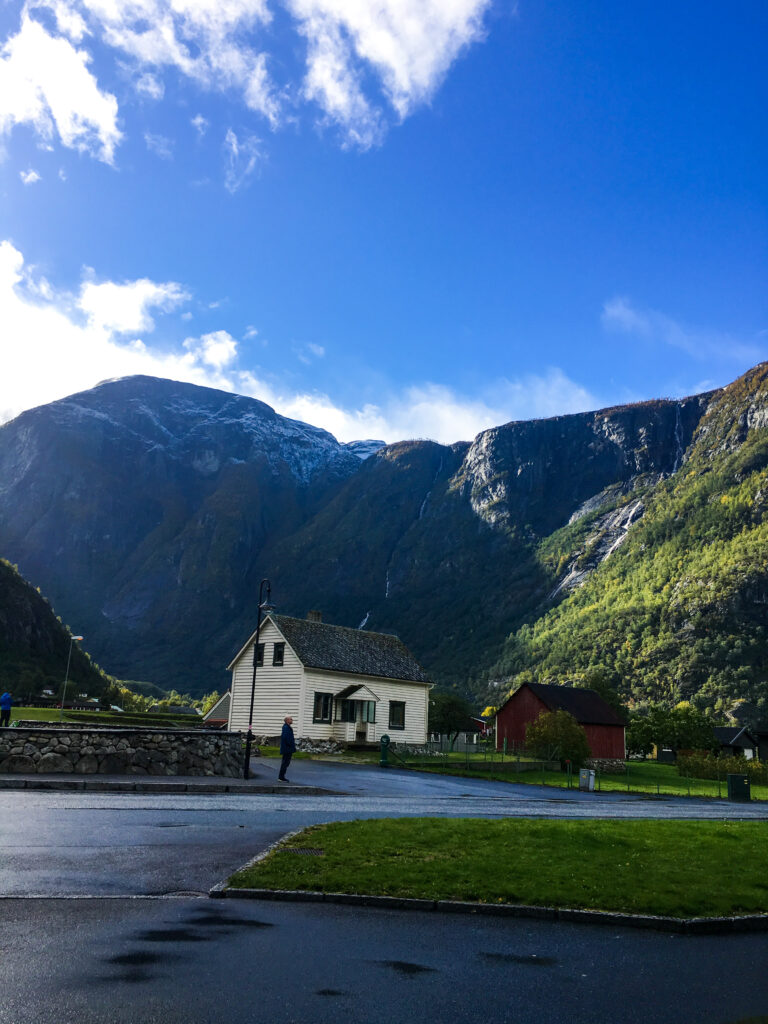 Two small Nordic houses in front of a towering snow capped mountain in eidfjord, Norway, part of a fjord tour from Bergen.