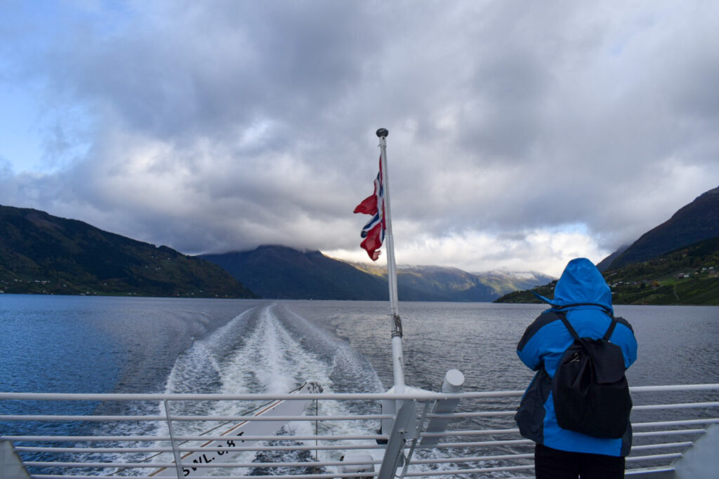 A woman in a blue rain coat stands on the deck of a boat cruising through Hardangerfjord in Norway. Spend one of your 5 days in Bergen exploring the surrounding fjords.