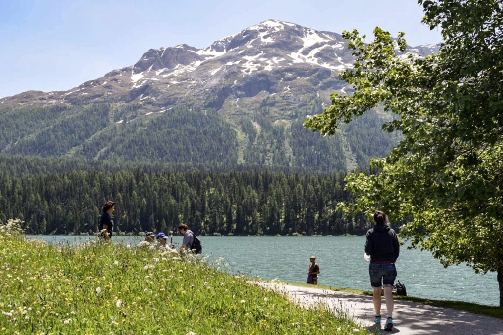 People gather around St Moritz alpine lake on the Bernina Express route, a great day trip to take from Milan.