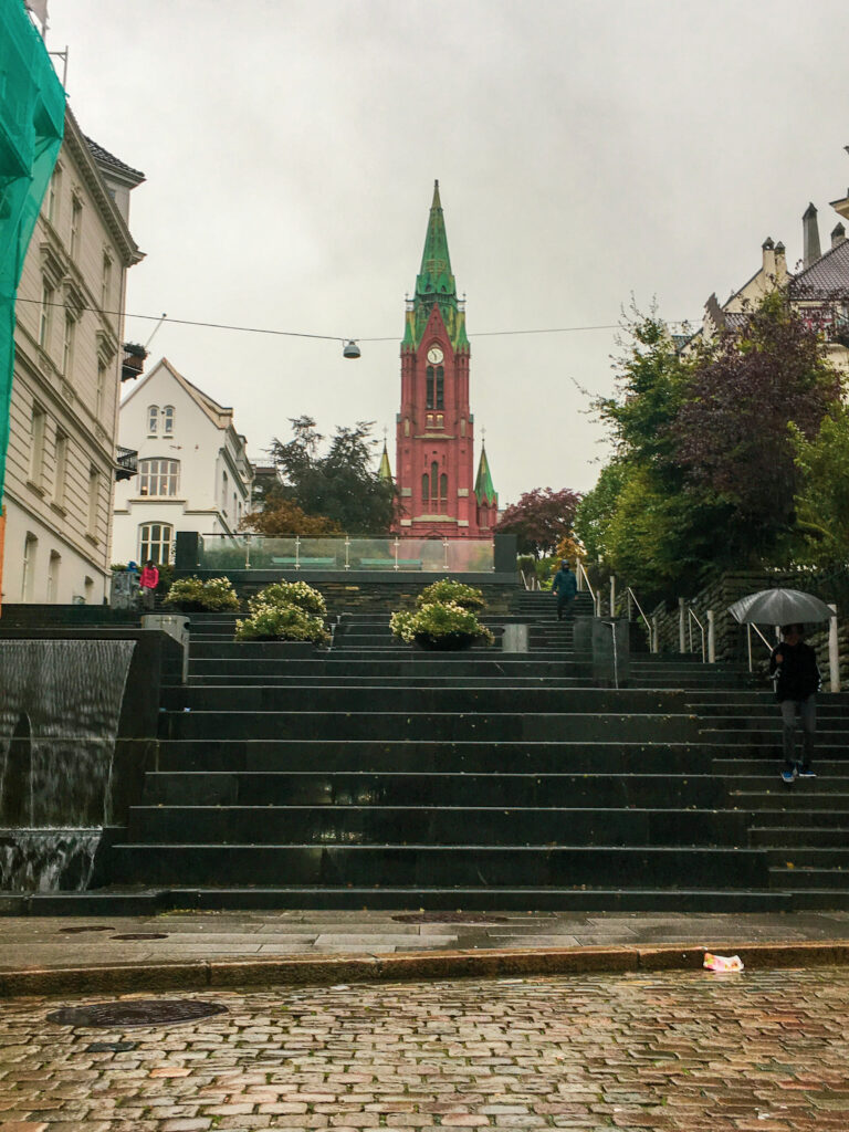 St John's church in Bergen in the city centre with stone steps leading up to it.