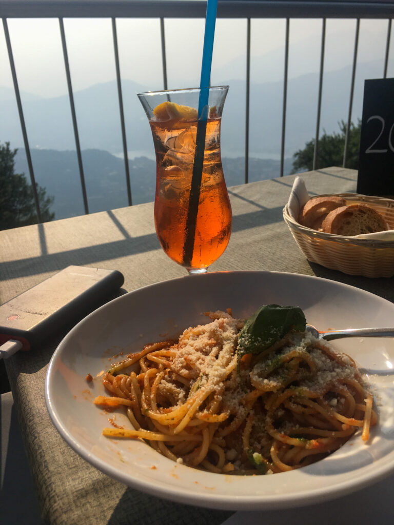 A plate of pasta with a cocktail with a view on top of Monte San Salvatore in Lugano.