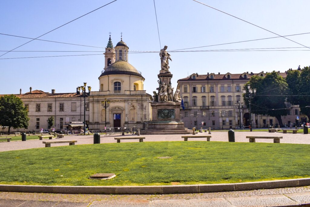 piazza carlo emanuele ii, a public square in Turin with park benches and a statue in the centre.