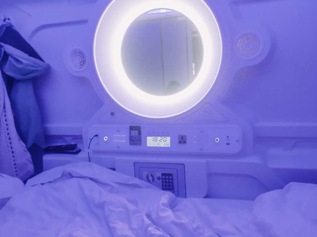 A blue-lit capsule room in Galaxy Pod hostel in Reykjavik. This is a great option for travel on a budget in Iceland.