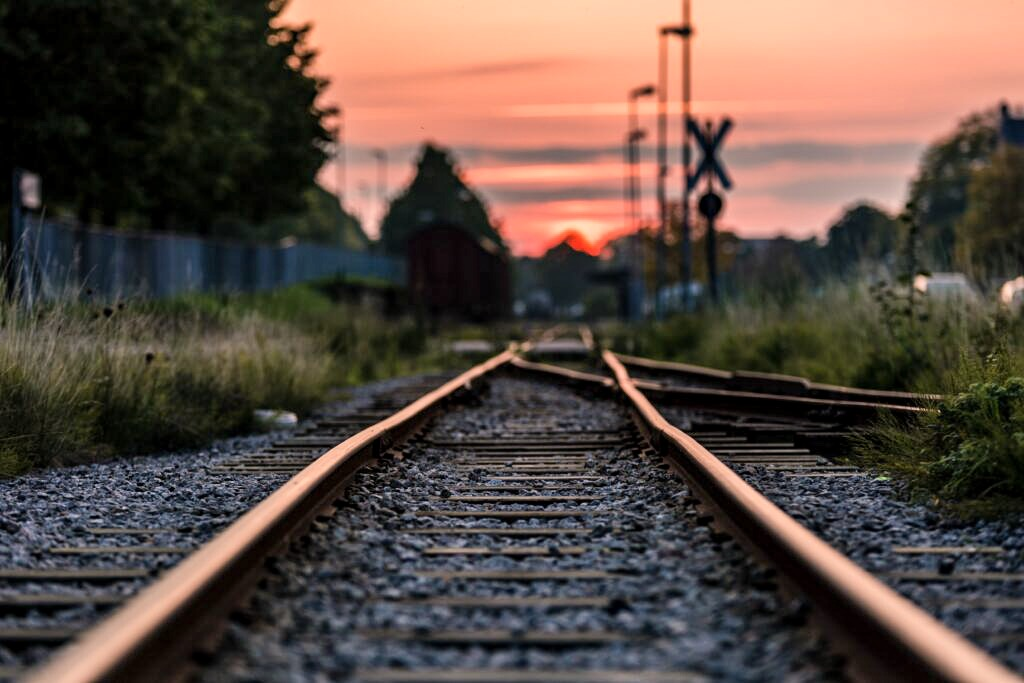 Sunset stock photo of train tracks. Find advice on buying tickets for the best day trips from Milan.