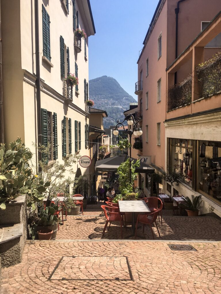 A pretty side street in Lugano, Switzerland lined with plants and restaurant chairs with mountain views in the background.