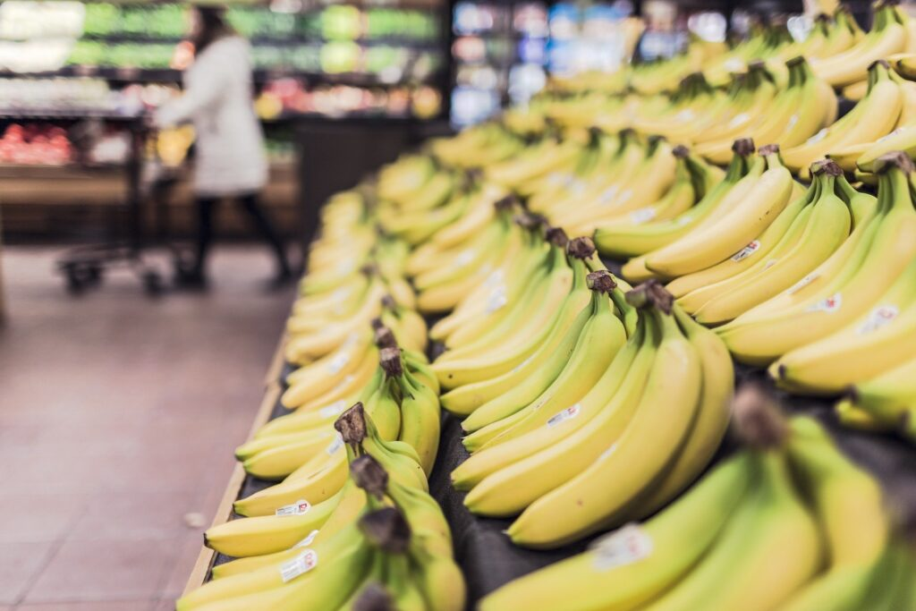 A stock photo of bananas in a supermarket. Buying and cooking your own food is essential to travel Iceland on a budget.