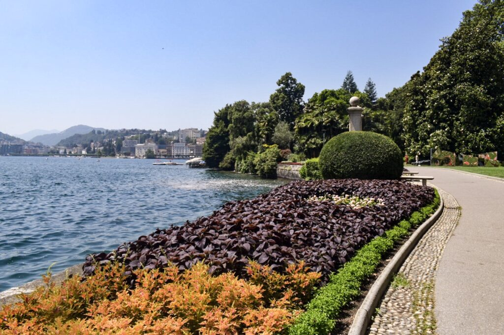 A lakeside path lined with flower beds in Parco Ciani in Lugano.