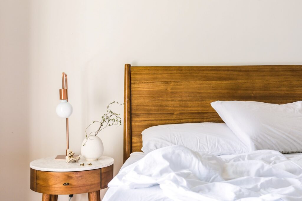 A wooden bed with white sheets in a hotel room or guest house. Disover the best accommodation options for travel in Iceland on a budget.