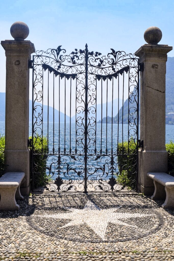 A decorative gateway with stone pillars leading to lake Lugano. Parco Ciani is a must do on a day trip from Milan to Lugano.