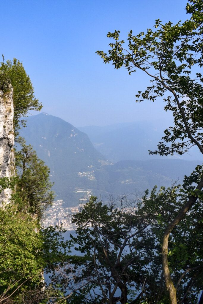 A view from of Lugano from Monte San Salvatore through some trees. Milan to Lugano is the perfect summer day trip.
