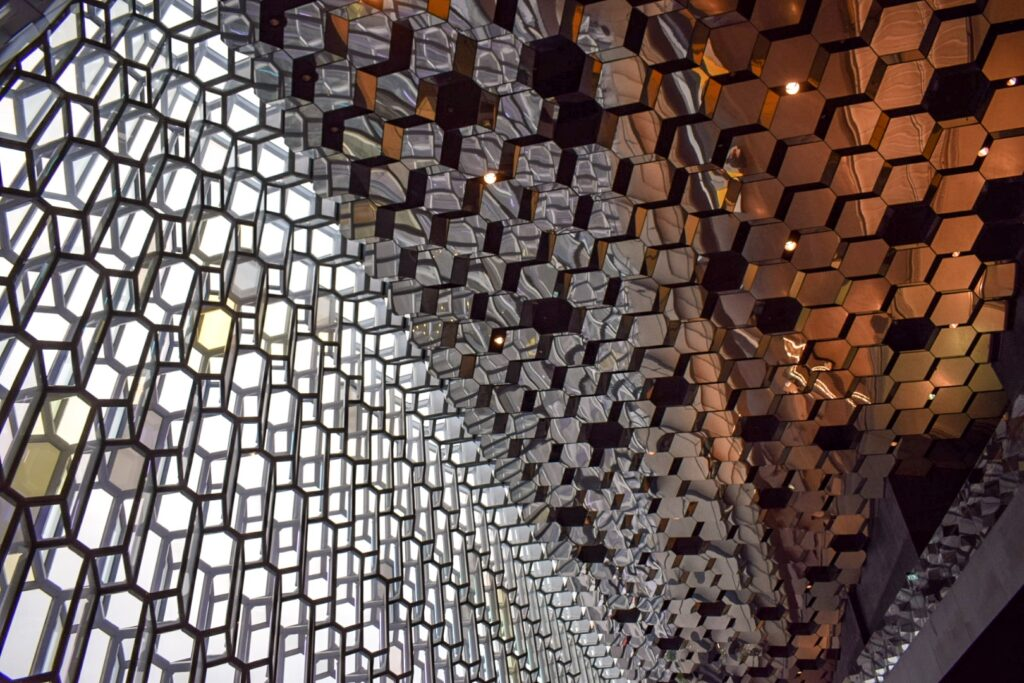 The inside of Harpa Concert hall in Reykjavik, with geometrically patterned stained glass windows and mirrored ceiling tiles. Harpa is a good thing to do in Oceland on a budget.