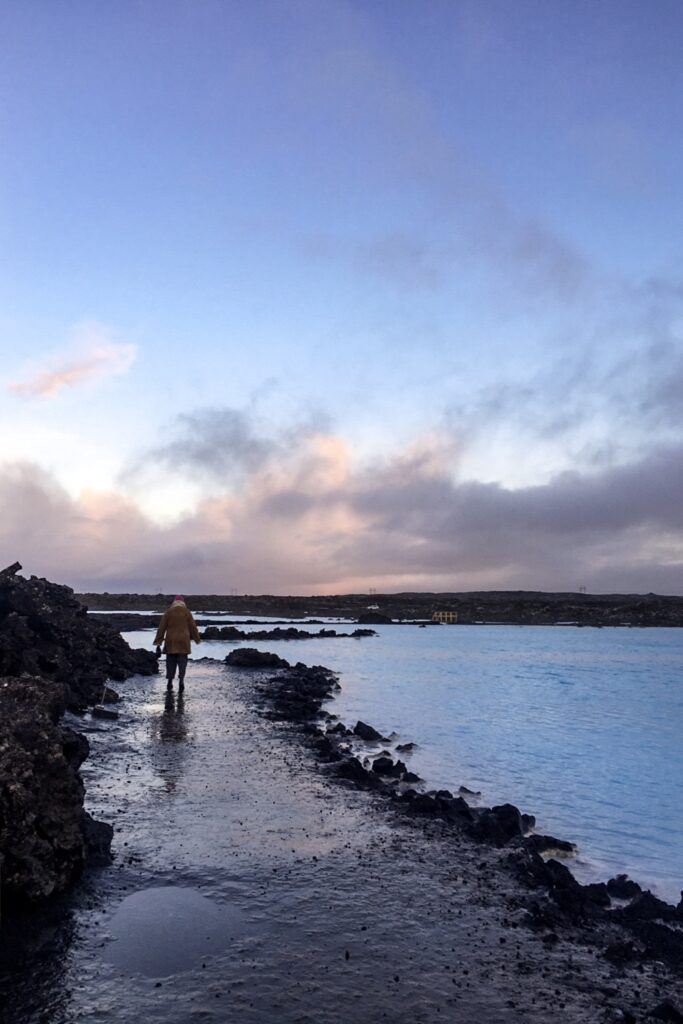 A person walking by the blue lagoon in Iceland.