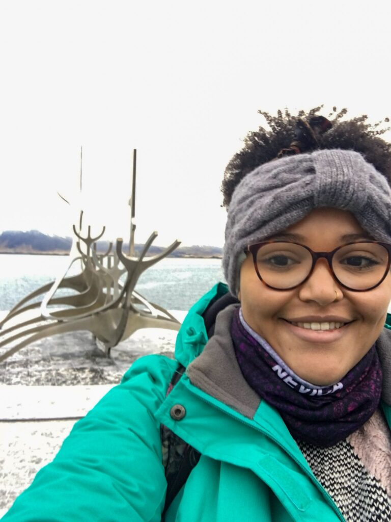 Imani stands smiling wrapped up warm in a green jacket, scarf and headband in front of the sun voyager sculpture in Reykjavik on a solo travel trip.