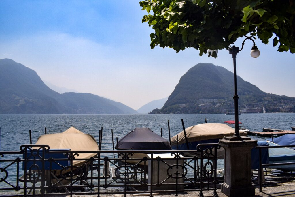 Covered boats at the shore of lake Lugano with a mountainous backdrop. Milan to Lugano is a great day trip.