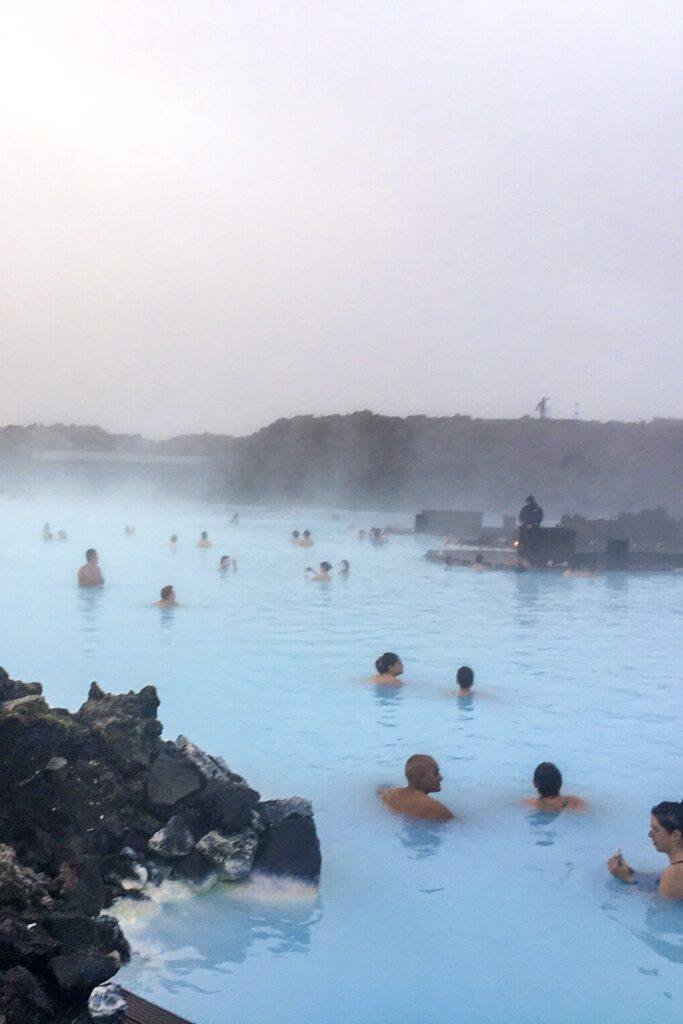People swimming in the blue lagoon in Iceland. Find out cheaper alternatives to the blue lagoon when travelling Iceland on a budget.