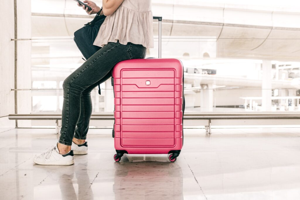 A girl sitting on a pink suitcase at an airport. Read for the best airport transfers in Iceland on a budget.