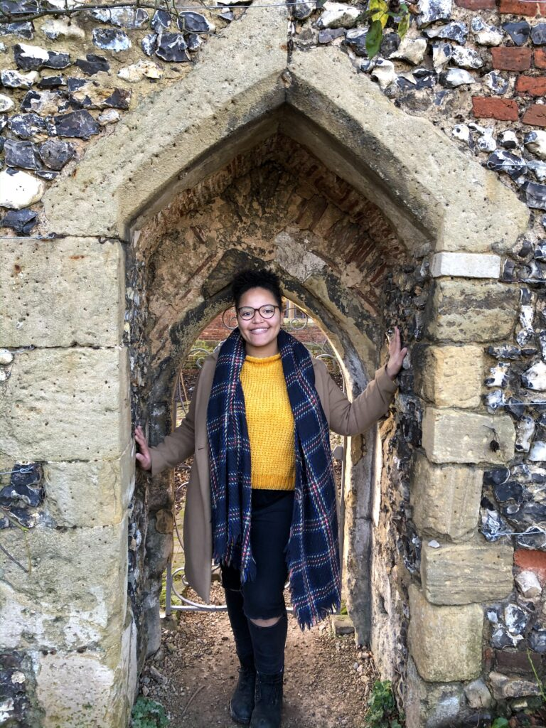 Imani stands in a narrow stone archway in England, wearing a bright yellow jumper and a blue scarf.