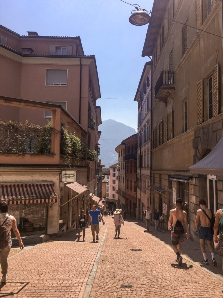 People walk through a narrow street lined with colourful houses in Lugano, a great place to visit from Milan.