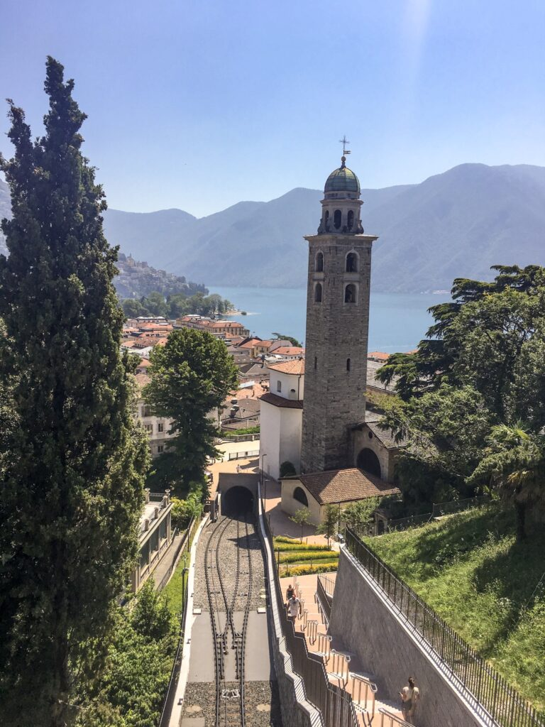 A view of Lugano from above, featuring Italian style villas, a church tower, a blue lake and green mountains. You can visit Milan in a day trip from Milan.