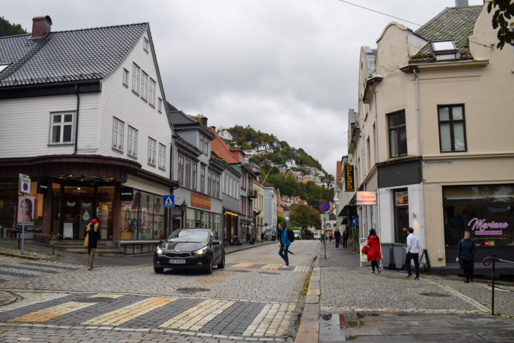 A car driving down a cobbled shopping street in Bergen. Spend one of your 5 days getting to know the city.