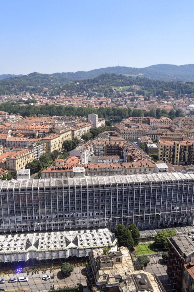The view of Turin from the mole, with terracotta Italian style rooftops and green rolling hills. Turin makes a great refreshing day trip from Milan.