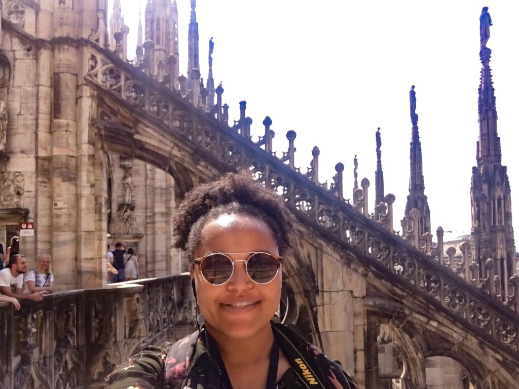 Imani stands smiling on the roof terraces of the Duomo cathedral in Milan on a solo travel trip.
