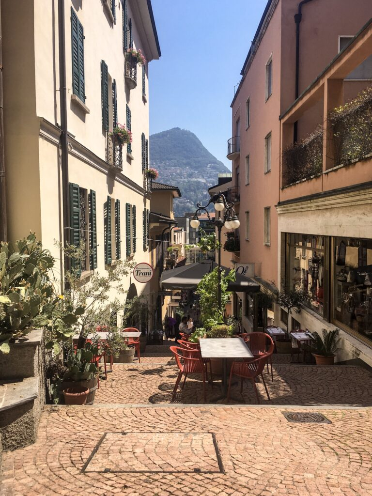 A pretty cobbled Street in Lugano with mountain views in the background. Milan to Lugano makes a great day trip.